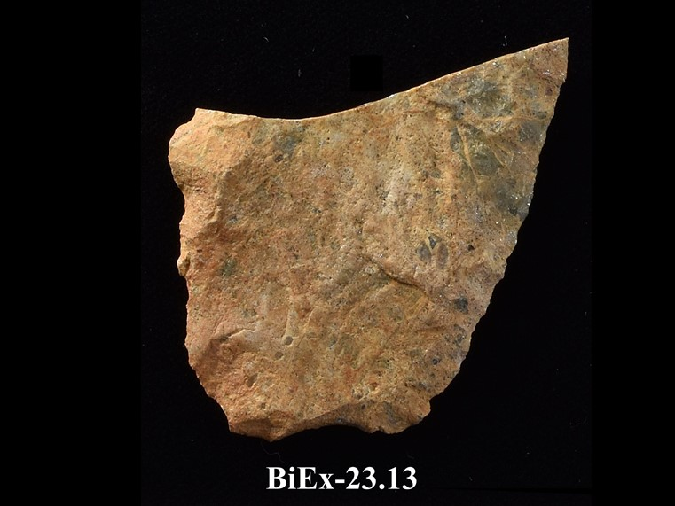 Fragment of beige chipped stone, with straight base and diverging edges. The top is broken at an oblique angle. The number BiEx-23.13 is inscribed on the bottom.
