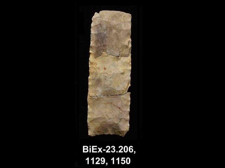 Three chipped stone shards, more or less square, placed one above the other, with parallel retouching on the edges. The number BiEx-23.206-1129-1150 is inscribed on the bottom.