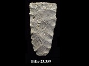Fragment of whitish, rectangular chipped stone, with a rounded base and sides with chipping marks. The number BiEx-23.359 is inscribed on the bottom.
