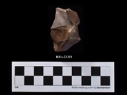 A block of reddish stone, more or less pyramidal, with a missing piece at its peak. The number BiEx-23.311 is inscribed on the bottom. Below the image is a photographic scale with black and white squares.